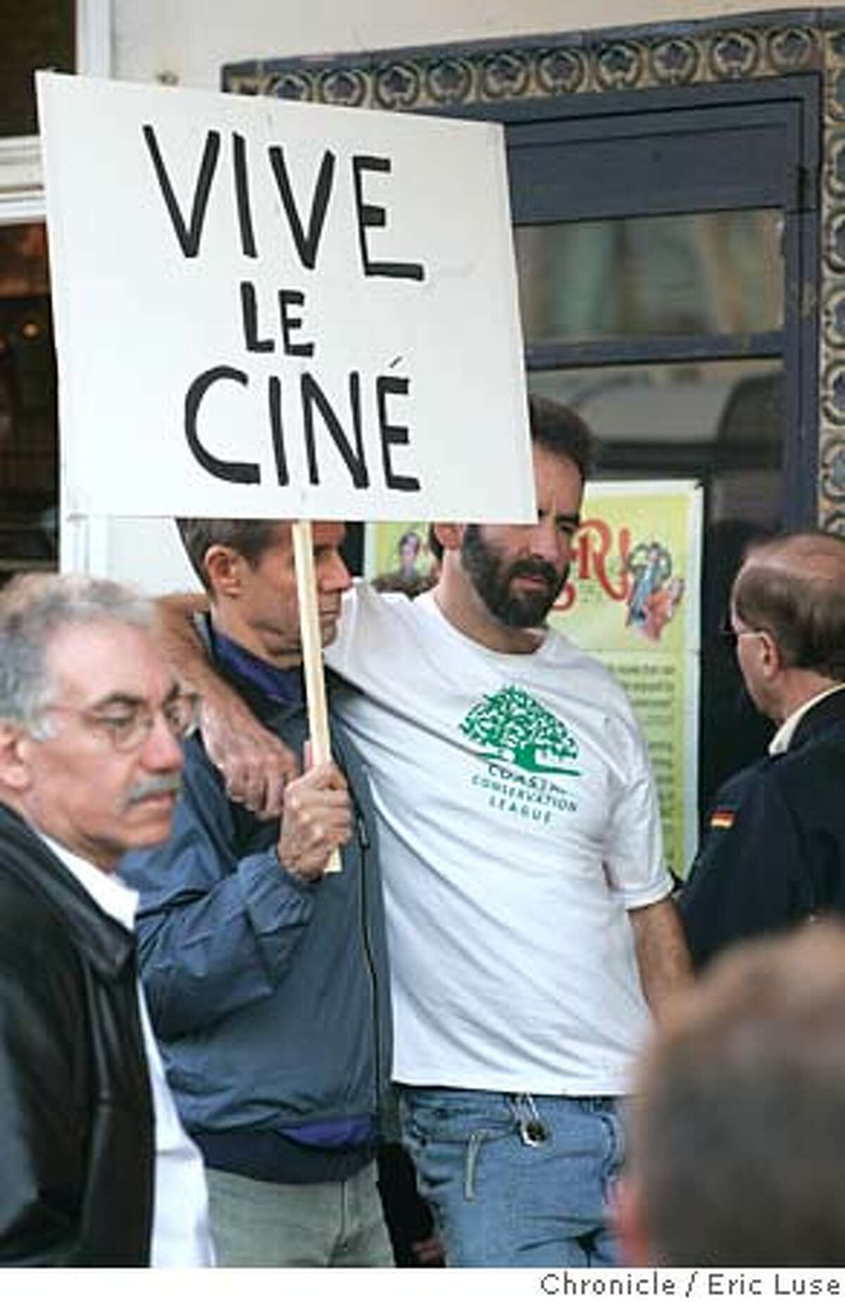 castro048_el.jpg l to r: Chuck Bierwirth and John Daniel, San Francisco, protesting in front of The Castro Theatre.far left (out of focus) is passing by. Protestors will gather from 3 to 5 pm. For the past 28 years, we have taken the Castro Theatre for granted. We always assumed it would remain a unique combination of beautiful movie palace and intelligent, innovative programming. But now this cultural treasure is in jeopardy. The owners' recent decision to dismiss Anita Monga, one of the top programmers in the country, has had repercussions that are only beginning to be felt. Filmmakers and distributors have pulled their films from the Castro's upcoming schedule. Because of Monga's abrupt departure, the Castro�s ability to present rare archival prints, re-released classics, and cutting-edge documentaries is imperiled. The Castro owners reportedly want to do more �family friendly� programming, and Ted Nasser, who�s currently running the theatre, has apparently been concerned with the gay content of some of the films Monga chose. Event on 12/18/04 in San Francisco. Eric Luse / The Chronicle Ran on: 12-19-2004 San Franciscans Chuck Bierwirth (left) and John Daniel (right) carry one sign at a protest staged by cinema fans upset over the firing of the Castro Theatres longtime programmer.