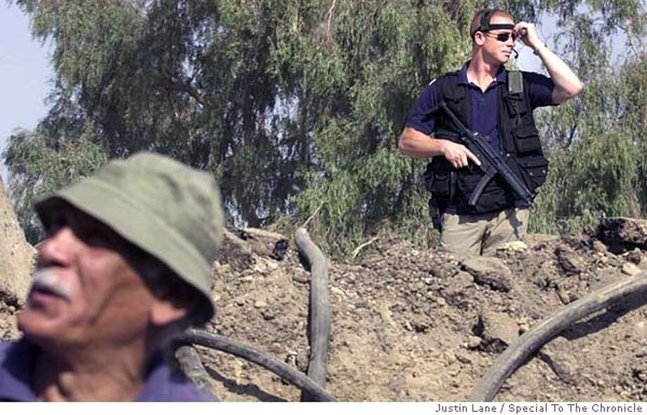 BECHTEL6.jpg 09/04/03--Bagdad, Iraq-- for David Baker Story  A member of the private security force hired by Bechtel to ensure safety in Iraq watches over a work site in Baghdad. The reconstruction of the phone system, as well as many other reconstruction projects, are being undertaken by Bechtel International Systems.  JUSTIN LANE FOR THE SAN FRANSISCO CHRONICLE ; on 9/4/03 in Baghdad. Justin Lane / Special To The Chronicle cat MANDATORY CREDIT FOR PHOTOG AND SF CHRONICLE/ -MAGS OUT Photo: Justin Lane