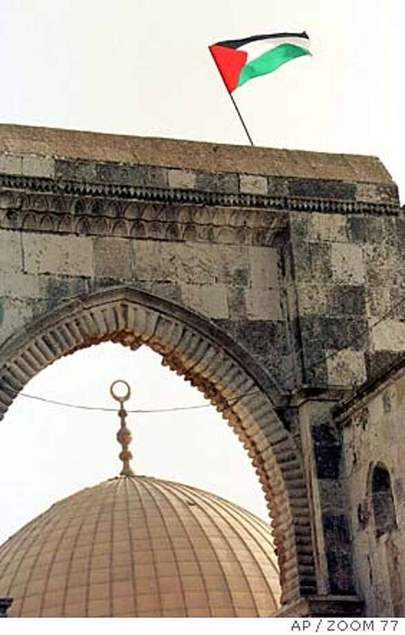 A Palestinian flag flies atop a gateway in the Al-Aqsa mosque compound, with the Dome of the Rock mosque seen in background, during riots Friday October 6, 2000. Israeli police stormed the bitterly contested Al-Aqsa mosque compound, also known as the Temple Mount, Friday and tore down Palestinian flags. (AP Photo/ZOOM 77) ISRAEL OUT COMMERCIAL ONLINE OUT ISRAEL OUT COMMERCIAL ONLINE OUT