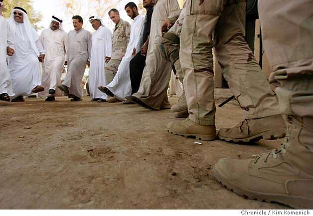 Soldiers join sheiks and wedding celebrants in a traditional line dance.  U. S. Army Lt. Col. Todd Wood and escort soldiers from the 2-7 Infantry Battalion of the 1st Brigade, 3rd Infantry Division (in Tikrit, Iraq) travel to the farm house of Sheikh Naji Al Jabouri in Jabaniya (about 20 miles northeast of Tikrit) where the sheikh's nephew and niece are getting married (yes, niece and nephew get married.) About 400 people attend the wedding including several area sheikhs.  San Francisco Chronicle photo by Kim Komenich Photo: Kim Komenich