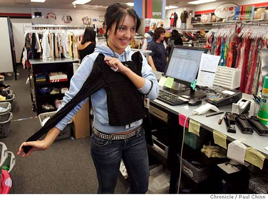 Employee Lyndsie Roy, 17, examines a blouse that a customer brought to the store hoping to sell. Shoppers browse the racks of used clothing at Plato's Closet on 6/4/05 in Dublin, Calif. The chain store's first shop in the Bay Area buys from and sells used brand name clothes to teens which is a tricky business; they have to read the trends and know what to buy and what to pass on.  PAUL CHINN/The Chronicle Photo: PAUL CHINN