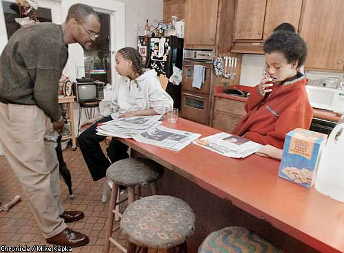 Oakland school board president Greg Hodge at his West Oakland home, spends time at the end of the day with his step dughter Imani Hinton-Lott and son Kumi Hodge, 13. BY MIKE KEPKA/THE CHRONICLE