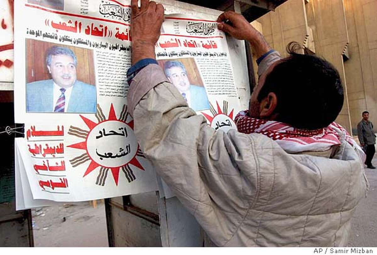 """A man hangs a list of candidates of a group of parties named """" Community Union"""" lead by Iraqi Communist Party leader Majeed Hameed, seen in the picture, for the upcoming January 30 elections, in Baghdad Wednesday Dec. 15 2004. (AP Photo/Samir Mizban)"""