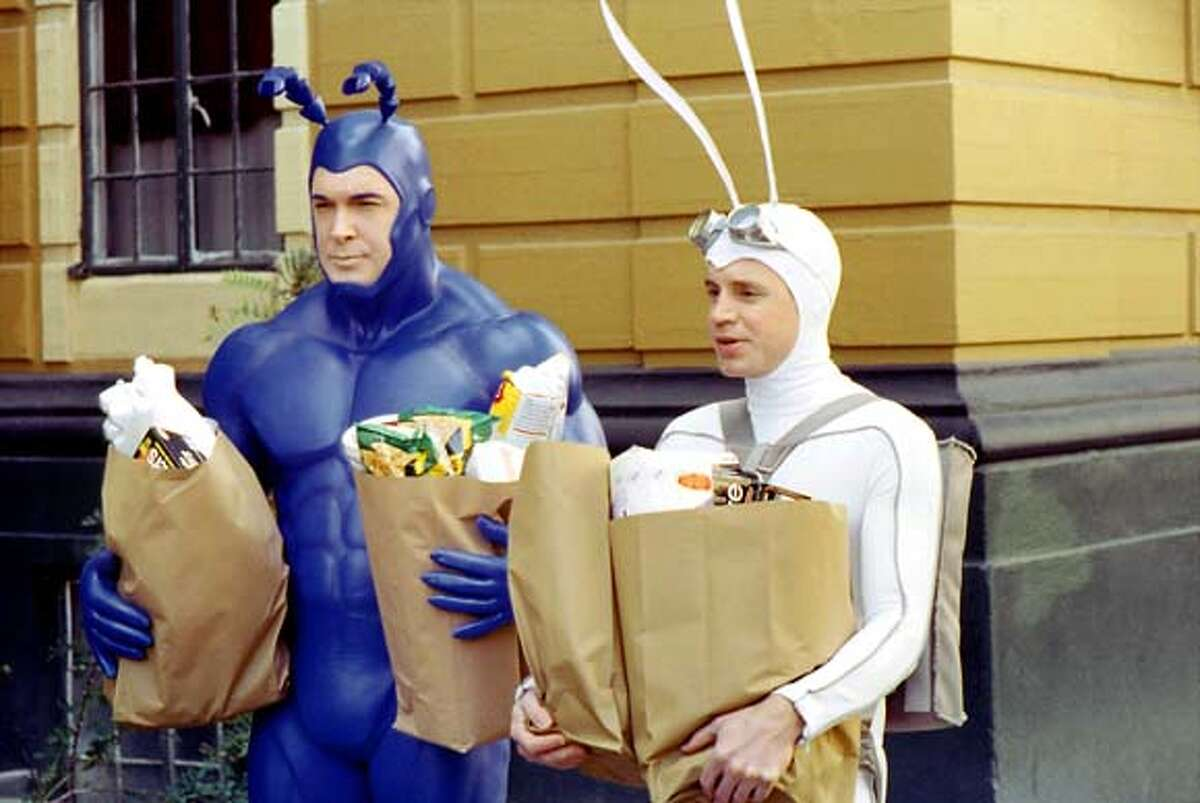 """Patrick Warburton, left, as the Tick, and David Burke as the Tick's sidekick, Arthur, haul their own groceries in this scene from the new Fox comedy series, """"The Tick."""" In the private lives of superheroes flows the lifeblood of the new sitcom, which airs Thursdays at 8:30 p.m., EST. (AP Photo/ 2001FOX BROADCASTING) A 2001 HANDOUT PHOTO."""