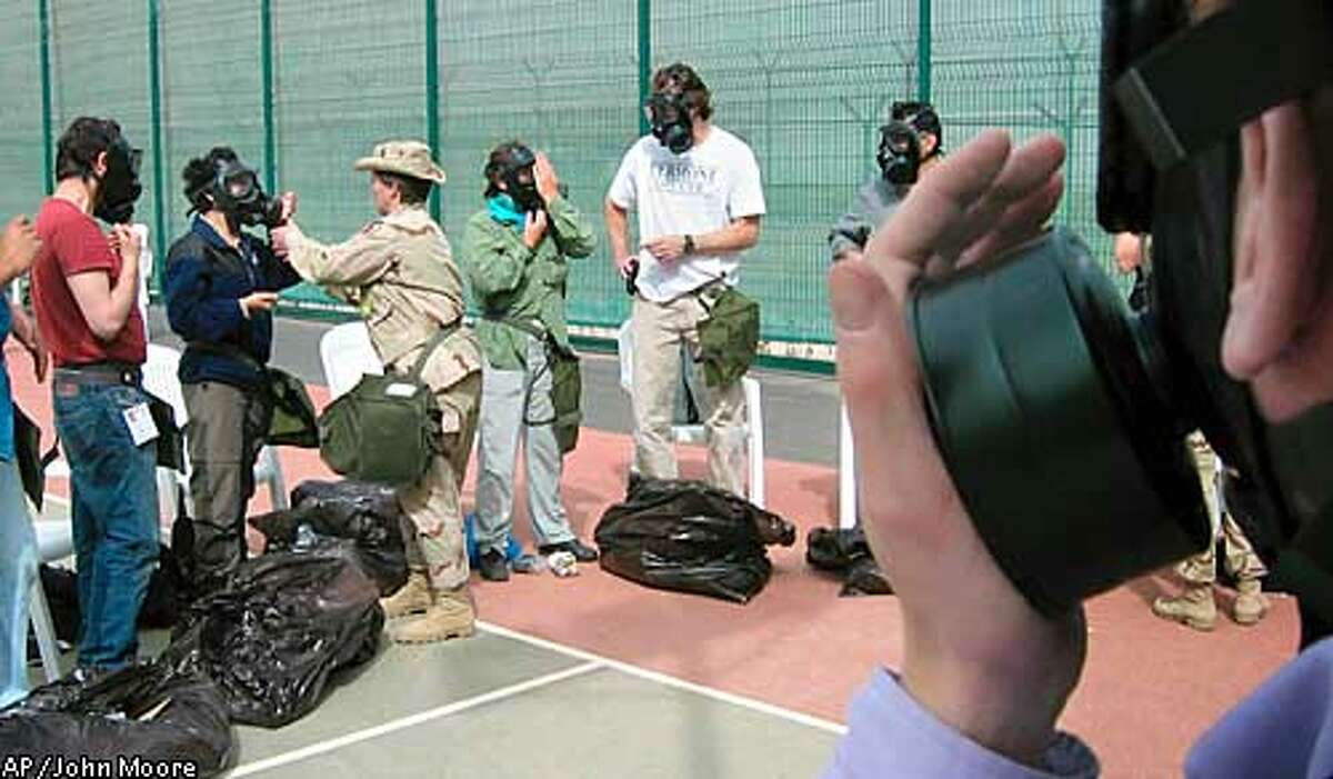 """Journalists receive gas-mask training for media """"embedding"""" with the Marines in Kuwait City Monday, March 10, 2003. More than 600 journalists are joining with military units to cover possible war with Iraq, and the military is providing chemical suits, gas masks and training for all media embedding. (AP Photo/John Moore)"""
