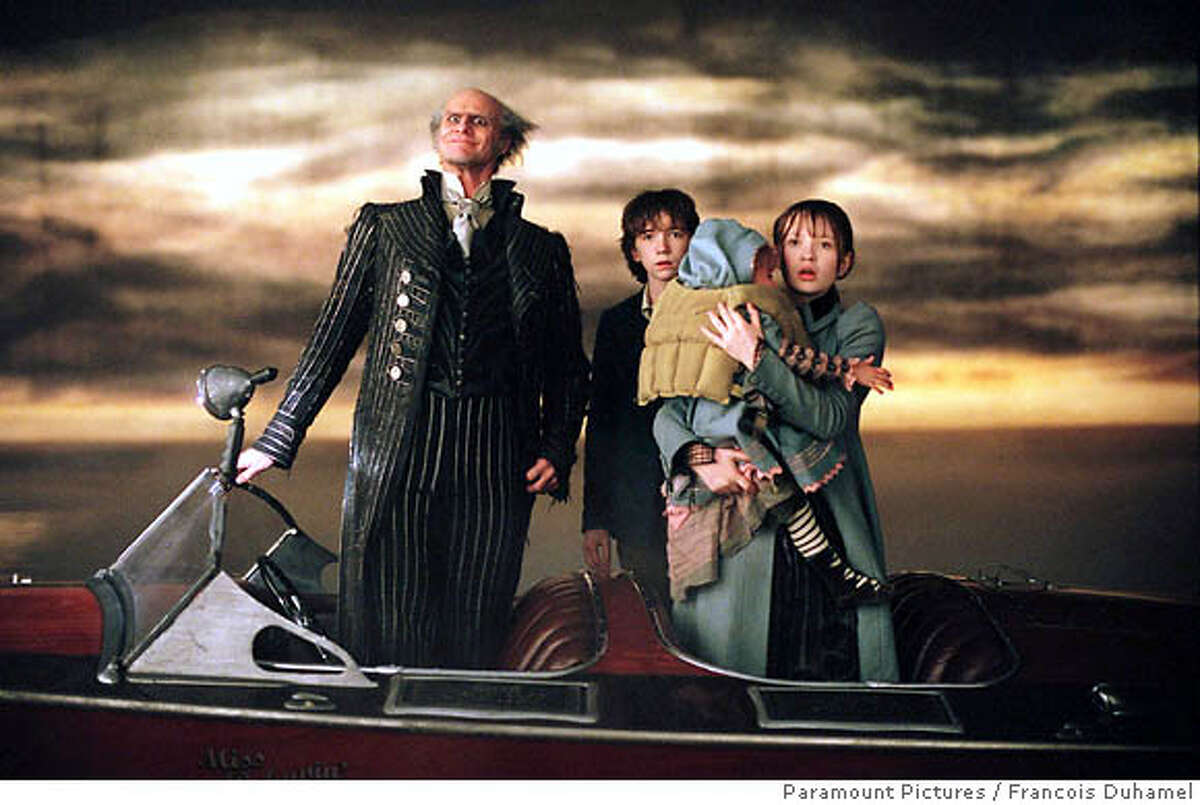 (NYT21) UNDATED -- DEC. 1, 2004 -- ADVANCE FOR SUNDAY, DEC. 5, 2004 -- CHILDREN-VIOLENCE -- From left, Jim Carrey as Count Olaf, Liam Aiken as Klaus and Emily Browning, right as Violet, holding Sunny in the forthcoming
