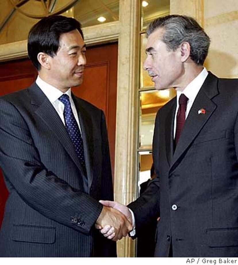 U.S. Commerce Secretary Carlos Gutierrez, right, is greeted by Chinese Commerce Minister Bo Xilai in Beijing Saturday, June 4, 2005. Gutierrez warned Bo of political pressures in the U.S. over trade with China, amid disputes about textiles and product piracy. (AP Photo/Greg Baker) Photo: GREG BAKER