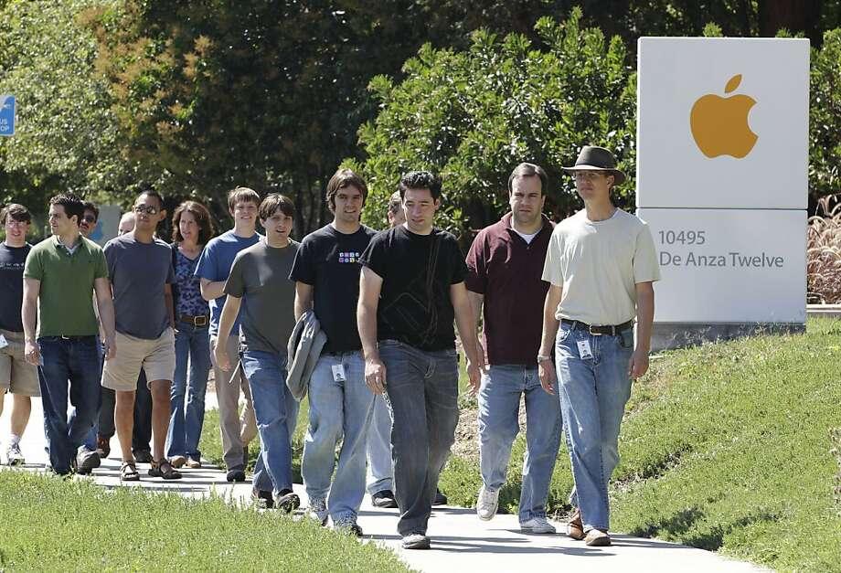 Apple employees walk between buildings at Apple headquarters in Cupertino. Photo: Paul Sakuma, Associated Press