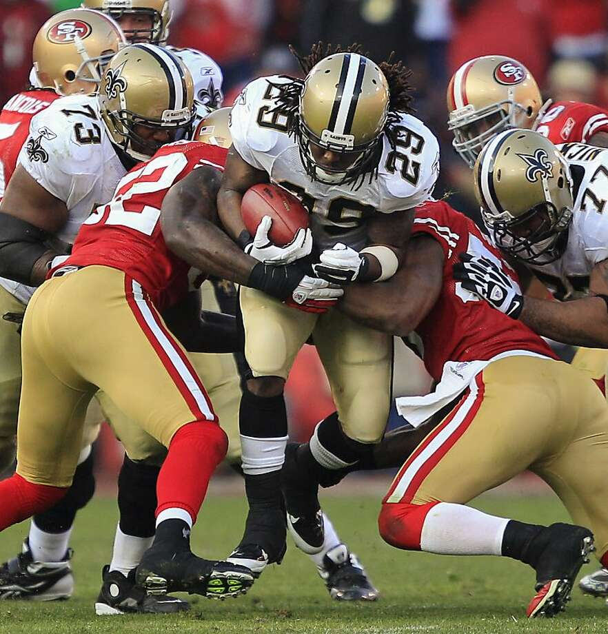 Patrick Willis (left) and NaVorro Bowman teamed up for 270 tackles, including this stop of Chris Ivory. Photo: Marcio Jose Sanchez, Associated Press