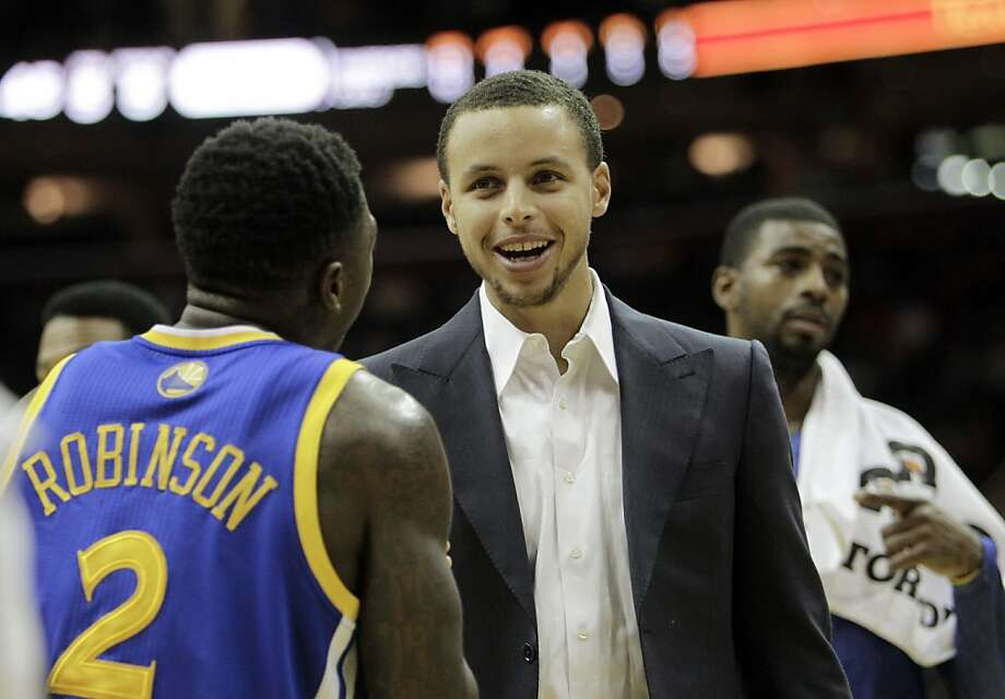Golden State Warriors' Stephen Curry, center, talks with Nate Robinson (2) during an NBA basketball game against the Cleveland Cavaliers Tuesday, Jan. 17, 2012, in Cleveland. (AP Photo/Mark Duncan) Photo: Mark Duncan, Associated Press