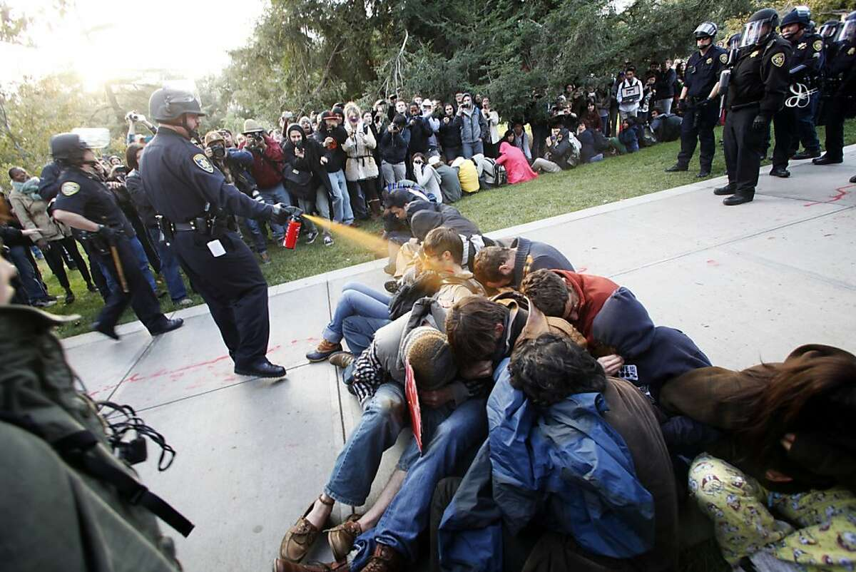 In this Nov. 18, 2011 file photo, University of California, Davis Police Lt. John Pike uses pepper spray to move Occupy UC Davis protesters while blocking their exit from the school's quad in Davis, Calif. The student body president at the University of California, Davis, where campus police pepper-sprayed peaceful demonstrators last fall, said students are angry over rising tuition and a lack of job prospects once they graduate. (AP Photo/The Davis Enterprise, Wayne Tilcock, File)
