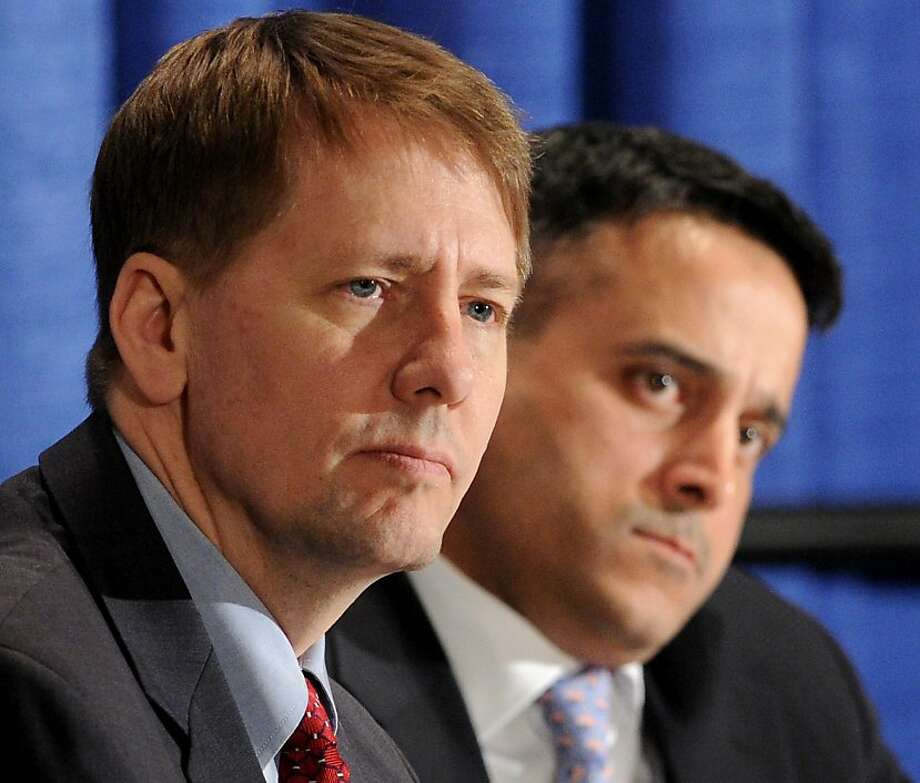 Director Richard Cordray of the Consumer Financial Protection Bureau, left, and Deputy Director Raj Date listen during a field hearing on payday lending in Birmingham, Ala., Thursday, Jan. 19, 2012.  (AP Photo/ The Birmingham News, Mark Almond) Photo: Mark Almond, Associated Press