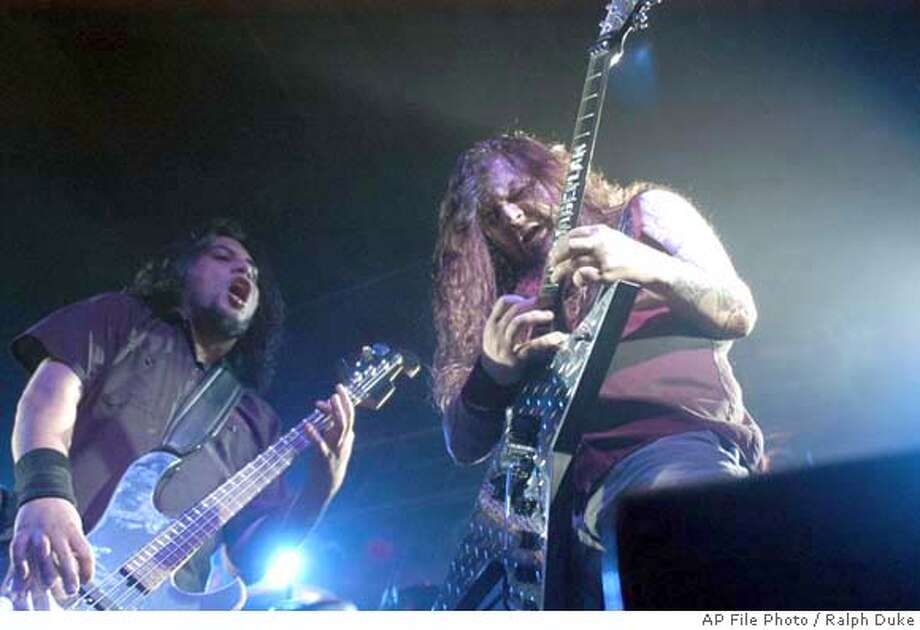 "**FILE**This a May 20, 2004, file photo of heavy metal band Damageplan guitarist ""Dimebag"" Darrell Abbott, right, and bass player Bob Zilla during a May 20, 2004 concert in Amarillo, Texas. Abbott was killed in Columbus, Ohio, Wednesday, Dec. 8, 2004, when a gunman charged onstage at a packed nightclub and opened fire on the band and crowd. (AP Photo/Ralph Duke, File) A MAY 20, 2004 PHOTO Photo: RALPH DUKE"