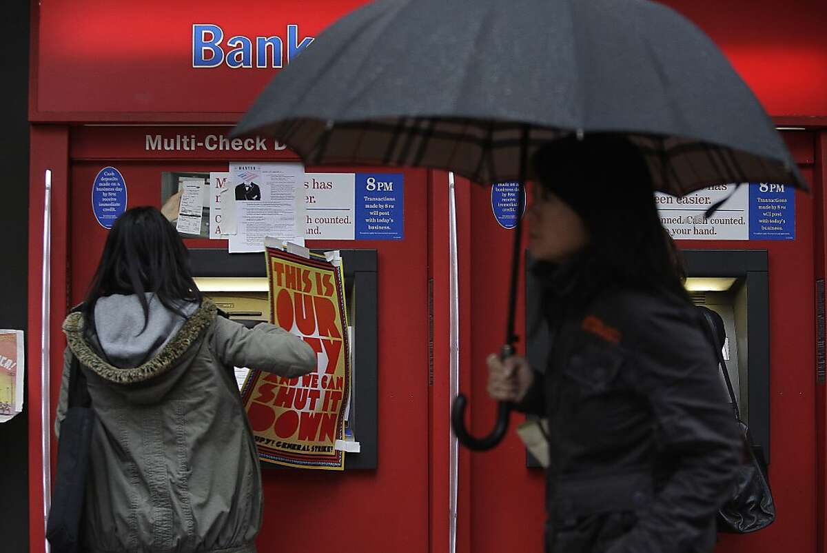 Kim Vu (left) removes a Occupy sign taped to an ATM so she can do her banking at the Bank of America on Market and Spear Streets where OccupySF Autonomous Action set up a food bank and served a free lunch on Friday, January 20, 2012 in San Francisco, Calif.