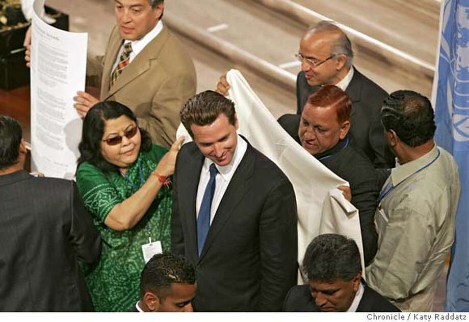 Closing ceremonies at San Francisco City Hall for the United Nations World Environment Day Conference. SHOWN: lady in green is Aneesa Begum Mirza, mayor of Ahmedabad, India--she joins Satbir Singh, mayor of Dehli, India, in draping a ceremonial gift shawl over SF mayor Gavin Newsom's shoulders--shawl handwoven in Kashmir of fine wool. Photo taken on 6/5/05, in SAN FRANCISCO, CA.  By Katy Raddatz / The San Francisco Chronicle Photo: Katy Raddatz