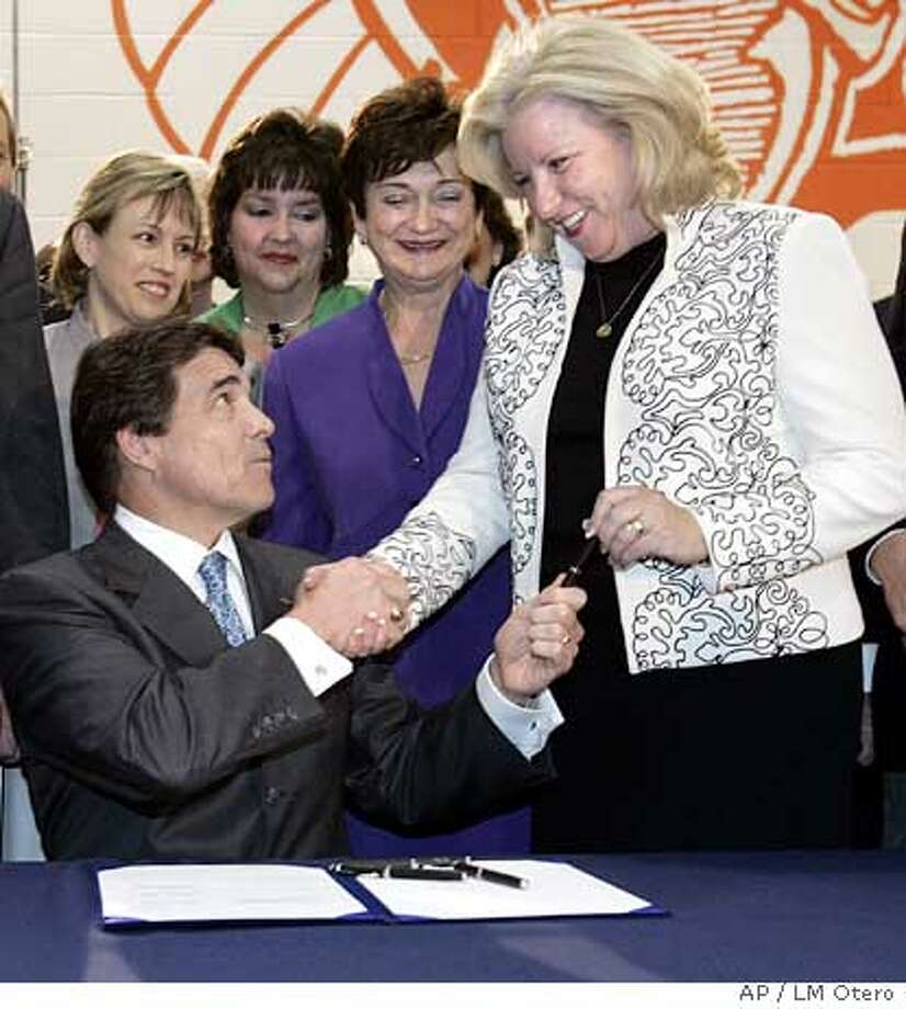 Texas Gov. Rick Perry, left, shakes hands with Sen. Jane Nelson, R-Lewisville, right, after signing the abortion consent bill during a ceremony in the gym of the Calvary Christian Academy in Fort Worth, Texas, Sunday, June 5, 2005. (AP Photo/LM Otero) Ran on: 06-06-2005  Texas Gov. Rick Perry and Republican state Sen. Jane Nelson exchange congratulations after the anti-abortion bill was signed. Photo: LM OTERO