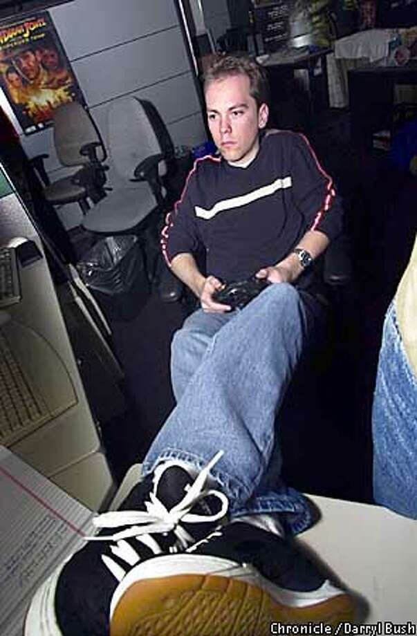"Andy Alamano, lead tester, sits with his feet up while testing video games in a dark cubicle in the ""test pit"" as they call it at LucasArts Entertainment CO. in San Rafael. Chronicle Photo by Darryl Bush Photo: Darryl Bush"