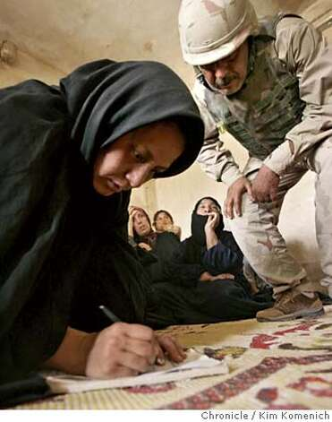 "Sajida Turki, sister of suspected insurgent Jamal Faluh Jasem, signs a receipt for $80 in reimbursement for a wall that soldiers demolished in a search for weapons.  Soldiers from Patrol Base Uvanni in Samarra, Iraq endure afternoon mortar attack as part of their day as they search suspected insurgents' homes, perform a ""cordon and talk"" ( where they hand out candy and toothpaste to kids in a neighborhood they cordon off), and look for suspicious cars using tanks to halt traffic.  San Francisco Chronicle photo by Kim Komenich Photo: Kim Komenich"