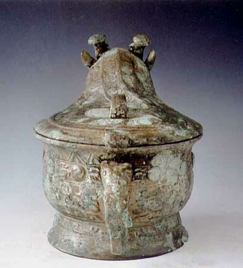 This lidded wine jar (you) was one of more than 90 bronze vessels associated with an elite burial in the Changzikou Tomb (Luyi county, Henan province). 52 lidded examples, including this one, were still a quarter- to half-full of liquid when the tomb was opened. Chemical analysis by Eric D. Butrym of Firmenich Corp. revealed that two aromatic compounds - camphor and alpha-cedrene - were present in the liquid, in addition to benzaldehyde, acetic acid, and short-chain alcohols characteristic of rice wine. Isotopic analysis by Michael P. Richards of the Max Planck Institute for Evolutionary Anthropology confirmed that the beverage was most likely rice-based. The aromatic compounds probably were derived from specific tree resins (e.g., China fir = Cunninghamia lanceolate Hook.), flowers (e.g., chrysanthemum spp.), and/or aromatic herbs (e.g., Artemesia argyi in the wormword genus). A single open vat, filled with leaves of Osmanthus fragrans and holding a ladle, was also found in the tomb. Possibly, the fermented beverage in the lidded containers of the tomb was steeped in the leaves, which have a floral aroma like the flowers that are used today in flavoring teas and beverages, and then transferred to the vessels. The rice wine in the vessel would have been made by saccharifying the grain sugars with molds, a uniquely Chinese contribution to fermented beverage-making. Photograph courtesy of Zhiqing Zhang, Institute of Cultural Relics and Archaeology of Henan Province, Zhengzhou, China. Photo: Handout