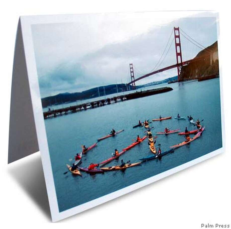 Seasonal greetings from local card firms include kayaks in the bay arranged as a peace sign from Palm Press in Berkeley. Photo courtesy of Palm Press