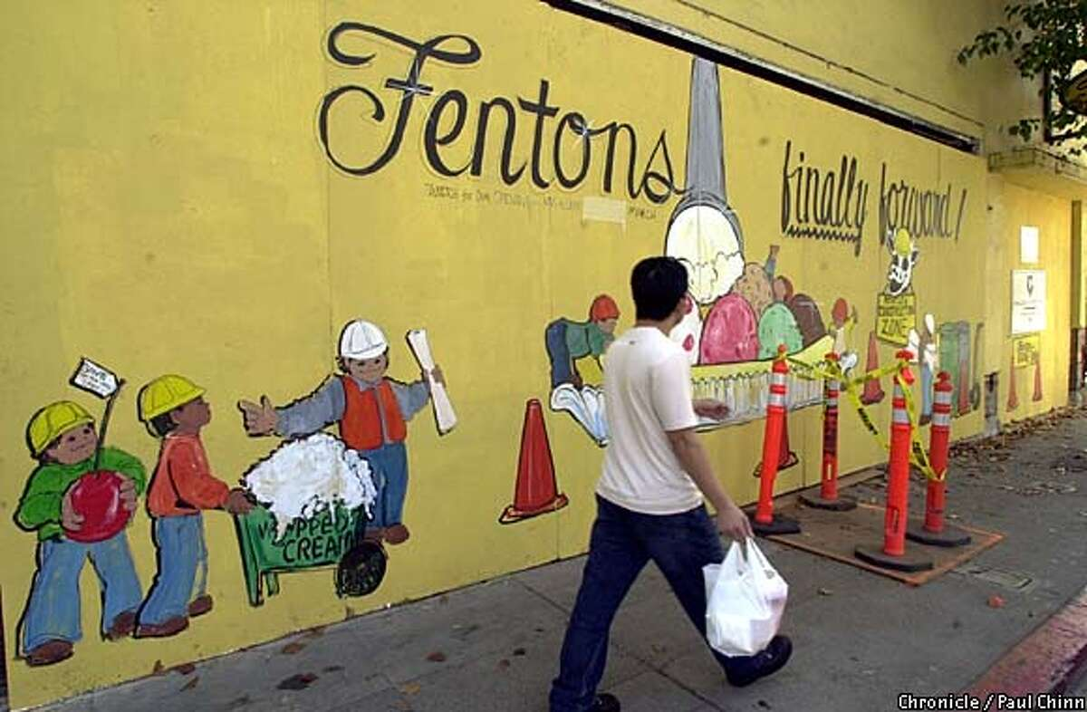 A pedestrian walks past the boarded-up facade. The rebuilding of Fenton's Creamery on Piedmont Ave. is underway after an arson fire gutted the popular ice cream parlor last year. PAUL CHINN/S.F. CHRONICLE