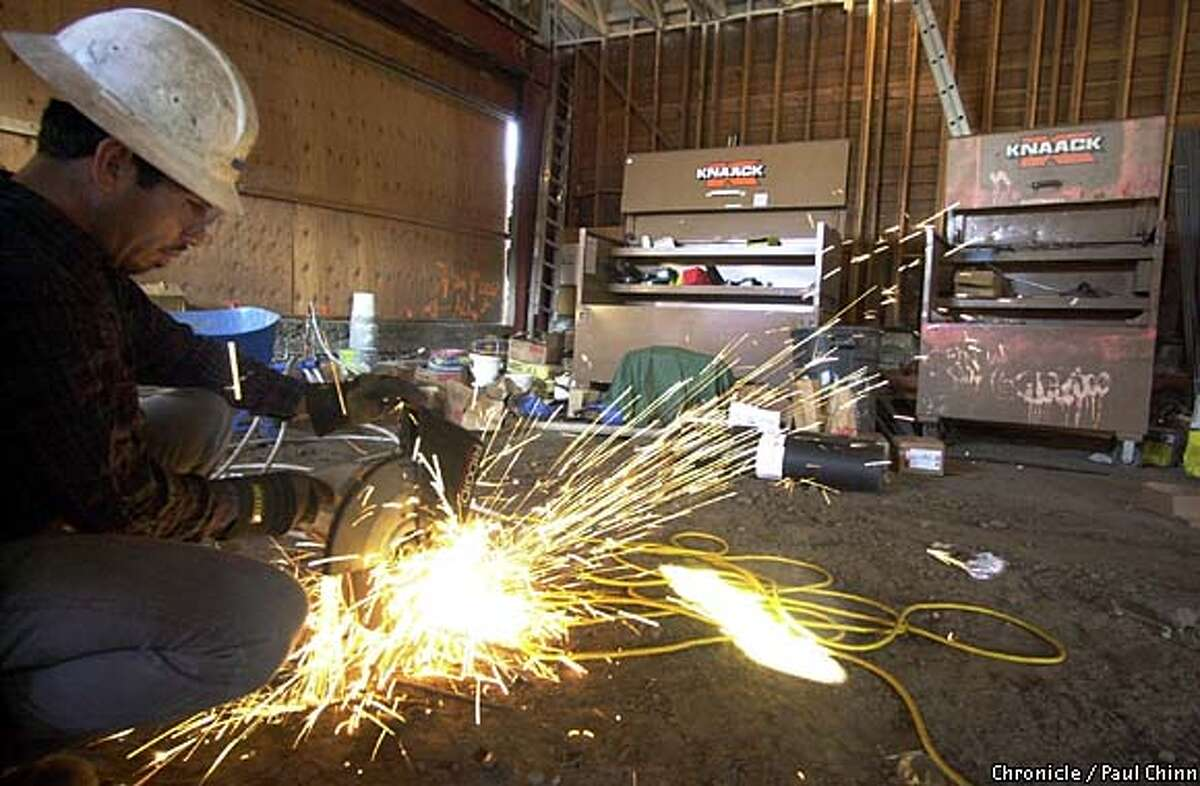 Sparks fly as a construction worker cuts steel rods. The rebuilding of Fenton's Creamery on Piedmont Ave. is underway after an arson fire gutted the popular ice cream parlor last year. PAUL CHINN/S.F. CHRONICLE