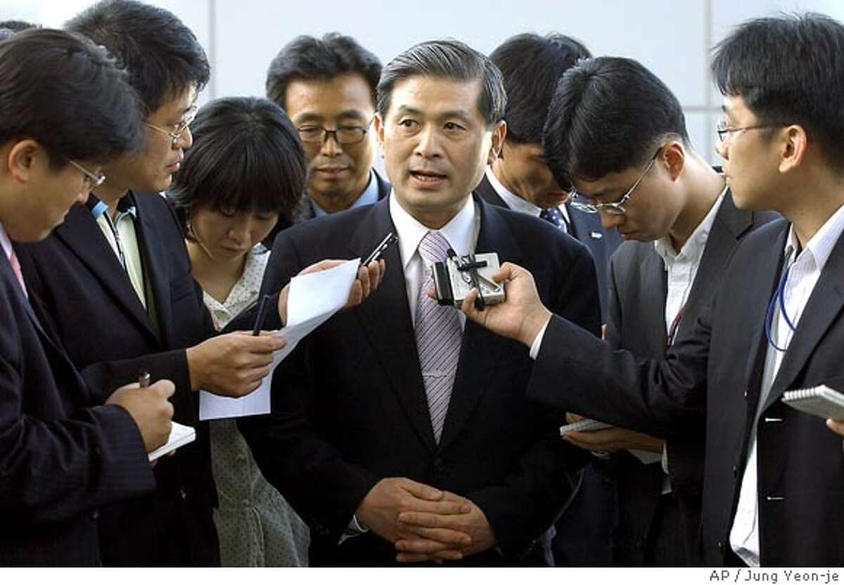 Seoul National University professor Hwang Woo-suk, center, is surrounded by journalists upon his arrival at the Incheon Airport, west of Seoul, Friday, May 20, 2005. South Korean scientists have dramatically sped up the creation of human embryonic stem cells, growing 11 new batches that for the first time were a genetic match for injured or sick patients. (AP Photo/Jung Yeon-je, Pool) POOL