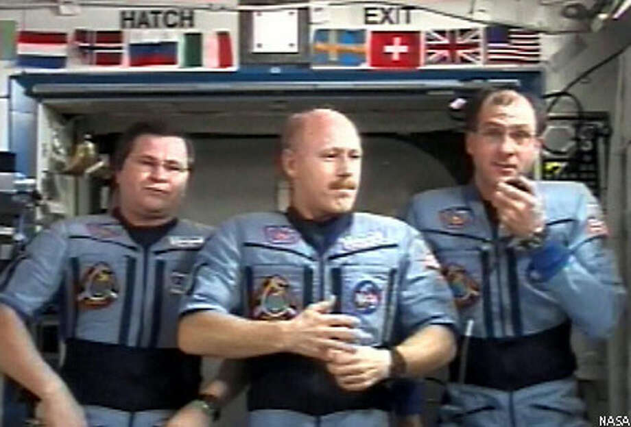 In the space station, science officer Donald Pettit, right, answers questions from reporters on Earth. He is joined by Russian flight engineer Nikolai Mikhailovich Budarin, left, and station commander Kenneth Bowersox. Photo courtesy of NASA
