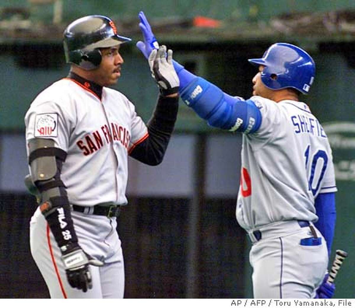 San Francisco Giants outfielder Barry Bonds (L) is congratulated by Los Angeles Dodgers outfielder Gary Sheffield (R) after Bonds hit a three-run homer in the fourth inning of the US-Japan All Star baseball game in Tokorozawa, suburb of Tokyo, 11 November 2000. The Major League Baseball All Star team defeated Japanese team 13-5. AFP PHOTO/Toru YAMANAKA Nation#MainNews#Chronicle#12/3/2004#ALL#5star##0422496891