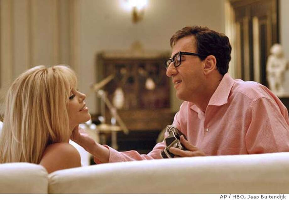 """In this undated publicity photo provided by HBO, Charlize Theron and Geoffrey Rush appear in a scene from the HBO film """"The Life and Death of Peter Sellers. Rush portrays Sellers and Theron, his second wife, Britt Ekland, in the movie premiering on the premium channel at 9 p.m., EST, Sunday. (AP Photo/HBO, Jaap Buitendijk ) Datebook#Datebook#Chronicle#12/3/2004#ALL#5star-dot##0422492411 Photo: JAAP BUITENDIJK"""