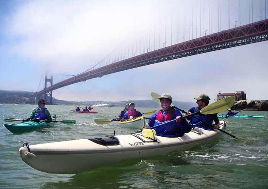 An ETC group paddles past the Golden Gate Bridge.
