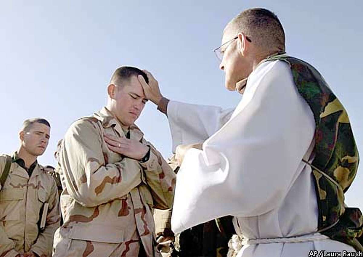 Father Bill Devine, right, of Boston, blesses Cpl. Nick Scyoc of McMinnville, Ore., during a Catholic Mass for the 1st Marine Expeditionary Force at Life Support Area 7 in the Kuwaiti desert south of Iraq on Sunday, Feb. 23, 2003. (AP Photo/Laura Rauch)