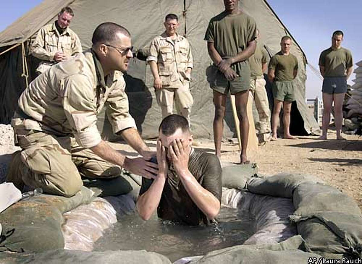 Chaplain David Slater baptizes Lance Cpl. Adam Hand of New Bader, Ill., during a Protestant service at Life Support Area 7 in the Kuwaiti desert south of Iraq on Sunday, Feb. 23, 2003. (AP Photo/Laura Rauch)