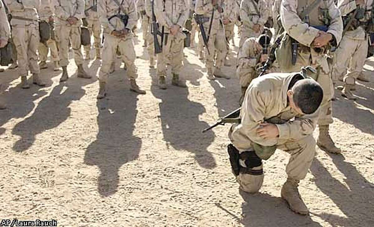 A U.S. Marine kneels after receiving communion during a Catholic Mass for the 1st Marine Expeditionary Force at Life Support Area 7 in the Kuwaiti desert south of Iraq on Sunday, Feb. 23, 2003. (AP Photo/Laura Rauch)