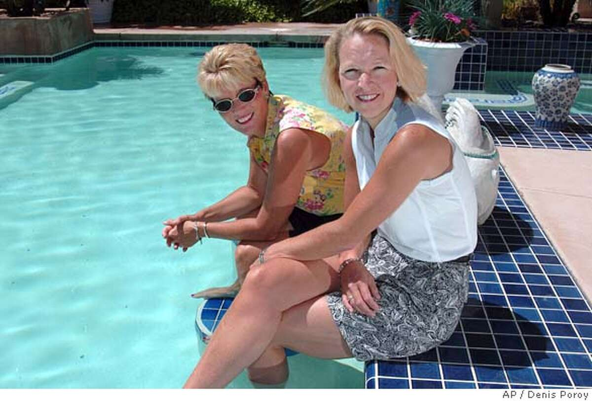 """Kendall French, right, and Birgit Koebke, left, sit next to their pool in the Tierrasanta neighborhood of San Diego, Sunday, May 22, 2005. The California Supreme Court heard opposing arguments Thursday, May 26, 2005, on whether private country clubs can refuse spousal discounts to lesbians whom by law cannot marry. The dispute centers on Birgit Koebke, who pays the Bernardo Heights Country Club Club in San Diego about $500 a month to continue her membership. Married members can have their children, grandchildren and spouses play golf for free. Under club rules, Koebke must pay as much as $70 for her partner, Kendall French, to play a round of golf, and French can only be Koebke's """"guest"""" six times a year. (AP Photo/Denis Poroy)"""