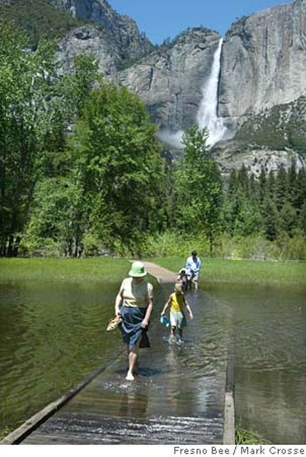 YOSEMITE, CALIF.-- -- 5/25/05-- -Ruth Showalter and daughter Petra, 7, of Waynesboro, PA., wade across a boardwalk that normally is high and dry, in the meadows adjacent to Yosemite Falls, in background. The valley is saturated with water, many of the meadows have been turned into ponds. MARK CROSSE-- -- FRESNO BEE 52605 Photo: MARK CROSSE