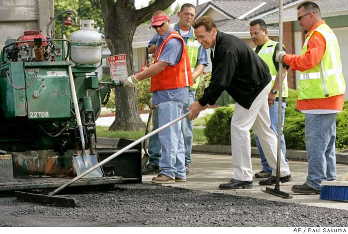 Calif. Gov. Arnold Schwarzenegger uses a tool to help grade a road in San Jose, Calif., as road workers watch, Thursday, May 26, 2005. Schwarzenegger discussed full funding of Proposition 42 transportation funds in his revised budget. (AP Photo/Paul Sakuma)