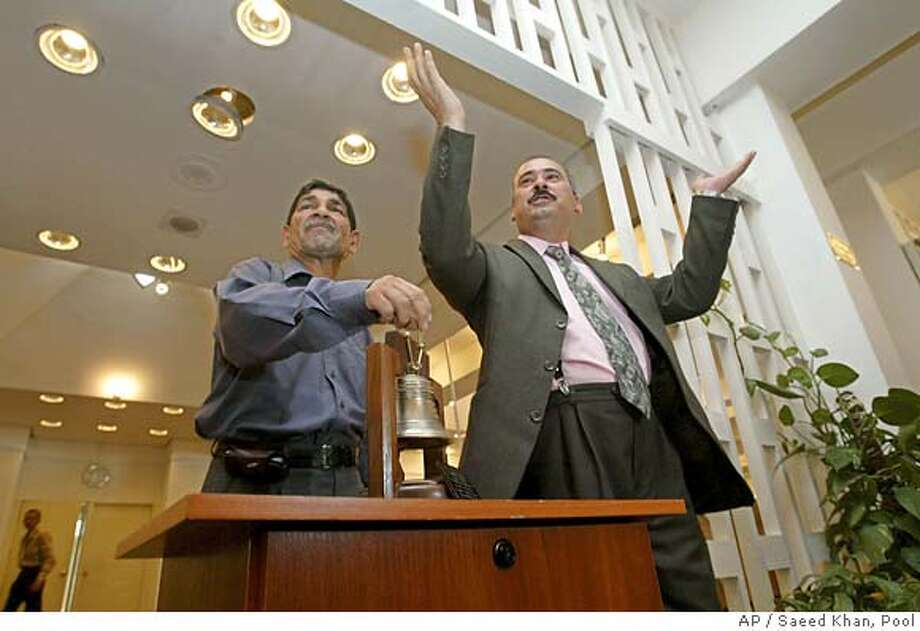 Talib al-Tabatabie, chairman of the Iraqi bourse, left, and Taha Ahmed Abdul Salam, acting chief of the bourse executive office, open a trading session at the well guarded stock exchange building in the center of Baghdad, Iraq, Sunday, July 18, 2004. At present, the Iraq stock exchange is open only on Wednesdays and Sundays from 10 am until midday, but plans are under way to create a six-day trading week. It only has 27 listed companies with about 100 more due to go public in the coming months. (AP Photo/Saeed Khan, Pool) DV Photo: POOL
