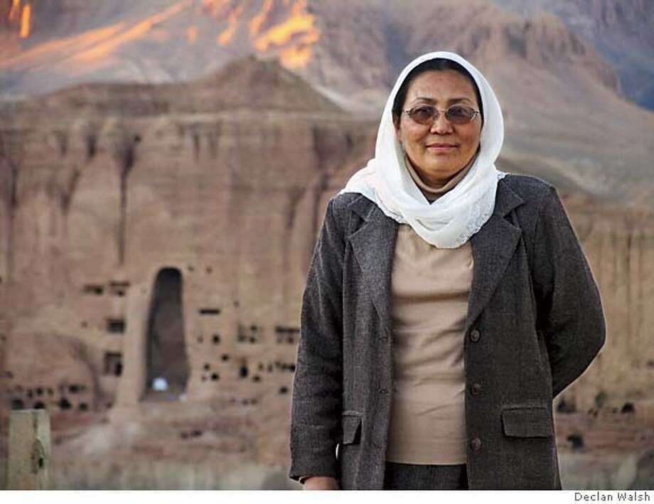 Habiba Sarobi, newly appointed governor of the central highland province of Bamiyan and Afghanistan's first woman governor, outside her office four days after starting her job. In the background is the caverns where the Taliban destroyed the famous Bamiyan Buddhas in 2000. March 05. By Declan Walsh