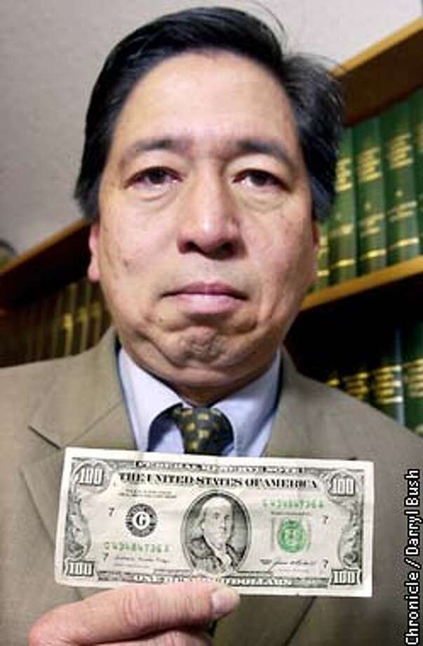 Attorney Rodel E. Rodis holds his 1984 one-hundred dollar bill that was alledged as counterfeit, in his office in San Francisco. He was arrested for passing the bill as counterfeit despite the fact the bill was legal tender. Chronicle Photo by Darryl Bush Photo: Darryl Bush