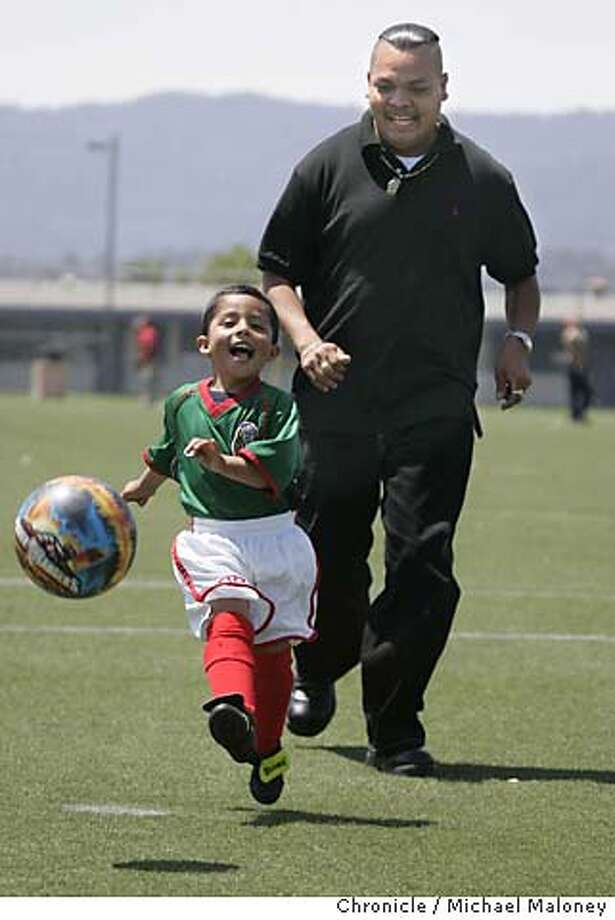 "Three year old Osvaldo (cq) Garcia and his dad Juan Garcia practice soccer at the Hoover School soccer field in Redwood City. ""Little Michoacan"" in Redwood City, part of the unincorporated North Fair Oaks neighborhood is 90 percent Latino. The modest homes, sandwiched among neighboring apartments and duplexes, have a distinct Latino flavor. Photo by Michael Maloney / San Francisco Chronicle Photo: Michael Maloney"