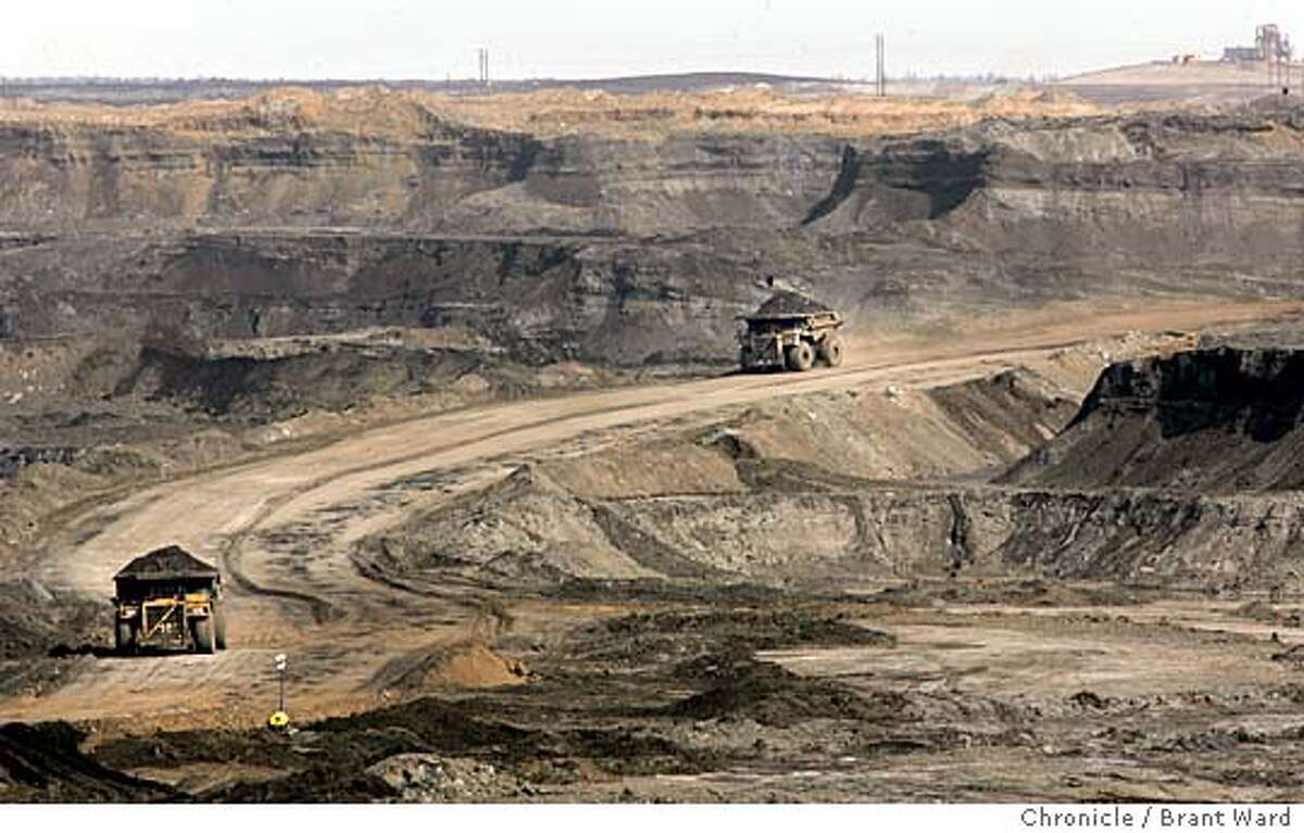 """At the Chevron oilsands project north of Fort McMurray, giant earth haulers drive into the canyon created by the strip mining process. They work 24 hours a day carrying the raw dirt coated with oilsands out of the manmade canyon. The oil sands area of Alberta, Canada is perhaps the answer to Canada and America's energy needs for the next 40 years. The oil is attached to tiny grains of sand and dirt and is being mined all around the city of Fort McMurray. This has caused a """"boomtown"""" atmosphere in the small town. Even with good salaries for workers at the oil sands, rents and home prices rival Northern California. Many of the """"homeless"""" make over $30,000 a year, but still can't afford the high rents. The young workers go a little crazy on weekends at the local casino and bars...the famous mounties must patrol outside. This is a portrait of the oil sands and the town that is paying the price. Brant Ward 4/20/05"""