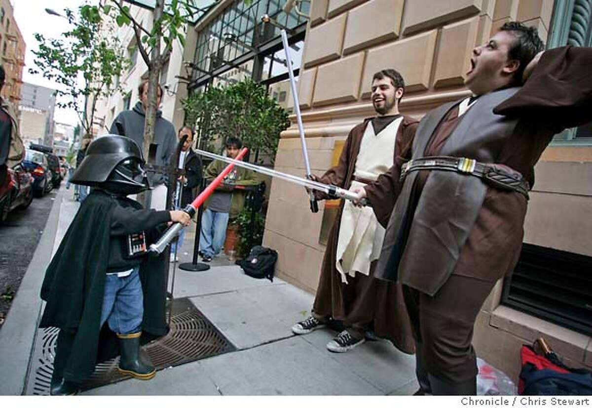 """starwarslines236.jpg Event on 5/18/05 in San Francisco. Peter Loeber (center), 21, SF, and David McCloughan (right), 21, SF, battle a young Darth Vader played by Giovanni Barreto, 4, as they await the midnight showing of """"Star Wars: Episode III - Revenge of the Sith"""" at the AMC Van Ness 14 Theater in SF. Giovanni is a """"third generation Star Wars fan,"""" according to his father Enrique Barreto, who was attending the movie with Giovanni and his grandfather. In anticipation of the Star Wars fanatics camping out outside of theaters hours before the first screening of Revenge of the Sith. Chris Stewart / The Chronicle MANDATORY CREDIT FOR PHOTOG AND SF CHRONICLE/ -MAGS OUT"""