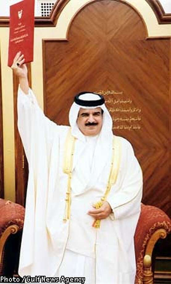 Bahrain's ruler, Sheik Hamad bin Isa AL Khalifa holds aloft a document at a ceremony giving his royal assent to constitutional amendments that made him king and the State of Bahrain the kingdom of Bahrian Thursday, Feb. 14, 2002 in Manama. Making its first steps on the road to democracy, the country was declared a constitutional monarchy Thursday, calling for national elections later in the year in which both men and women will be allowed to vote and run for office. (AP Photo / Gulf News Agency)