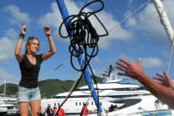 """Dutch sailor Laura Dekker throws a rope as she docks her boat in Simpson Bay Marina in St. Maarten, Saturday Jan. 21, 2012.  Dekker ended a yearlong voyage aboard her sailboat named """"Guppy"""" that made her the youngest person ever to sail alone around the globe, although Guinness World Records and the World Sailing Speed Record Council did not verify the voyage, saying they no longer recognize records for youngest sailors to discourage dangerous attempts. (AP Photo/Stephan Kogelman)"""