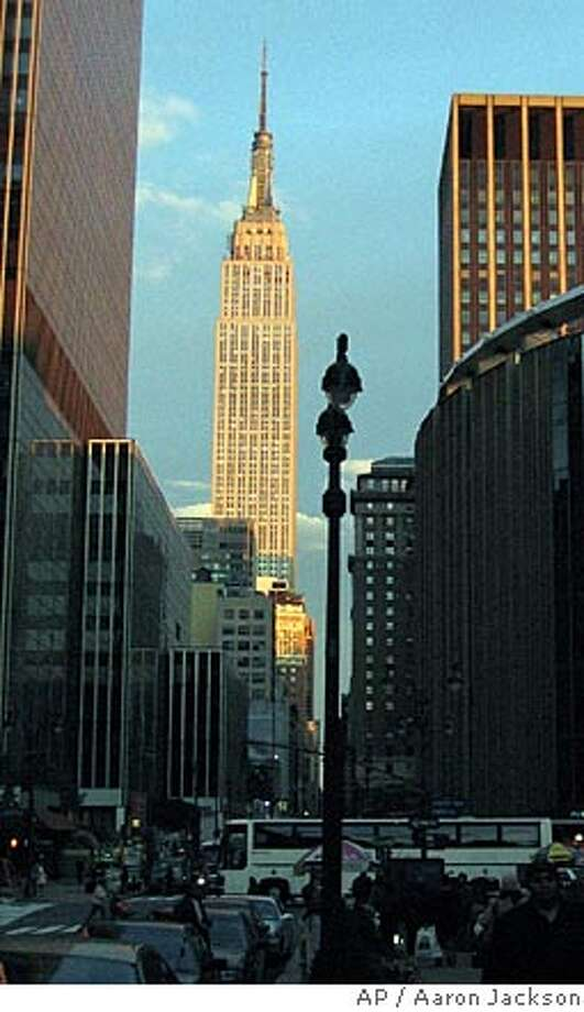 TRAVEL ** FILE **The setting sun reflects off New York's Empire State Building in July 2004. If you do not want to wait two hours and pay $13 on a beautiful day to wait on line to go up to the top of the famous skyscraper, instead enjoy looking at it from afar. (AP Photo/Aaron Jackson/FILE) Photo: AARON JACKSON
