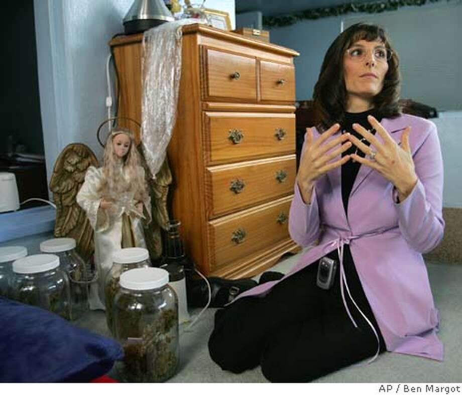 Angel Raich gestures beside jars of marijuana at her home Friday, Nov. 5, 2004, in Oakland, Calif. Legal drugs have done little to help Raich. Beset by a nightmarish list of ailments that includes tumors in her brain and uterus, seizures, spasms and nausea, she has been able to find comfort only in the marijuana that is prescribed by her doctor. (AP Photo/Ben Margot) Metro#MainNews#Chronicle#11/28/2004#ALL#5star##0422485706 Photo: BEN MARGOT