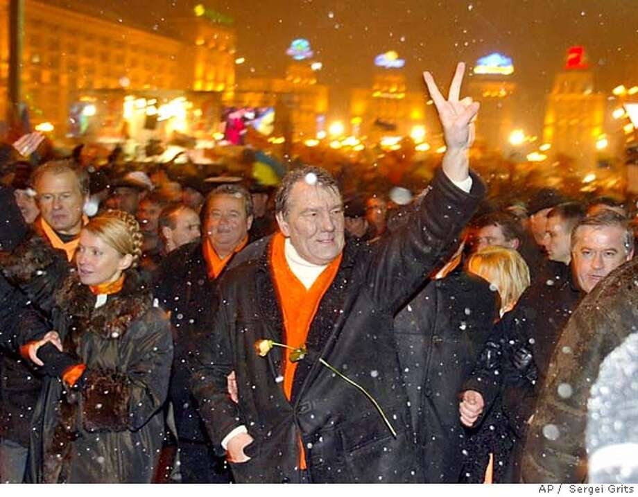 Ukraine's key opposition leader Viktor Yushchenko makes a V-sign as he walks through a street to the Ukrainian Presidental administration building in Kiev, Tuesday, Nov. 23, 2004. At left is Yushchenko's top ally Yulia Timoshenko. ( AP Photo/ Sergei Grits) Nation#MainNews#Chronicle#11/24/2004#ALL#5star##0422482375 Photo: SERGEI GRITS