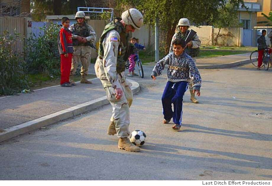 INSIDEIRAQ20 Soldiers play soccer with Iraqi kids in Balad, Iraq. Inside Iraq: The Untold Story. CR: Mike Shiley