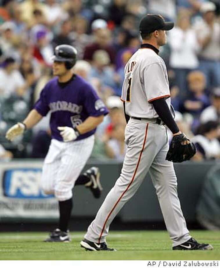 San Francisco Giants starting pitcher Noah Lowry, front, looks to the left-field corner as Colorado Rockies' Matt Holliday, back, circles the bases after hitting a solo home run off Lowry to lead off the second inning in Denver on Tuesday, May 17, 2005. Lowry followed up by giving up a solo home run to the Rockies' Todd Greene. (AP Photo/David Zalubowski) Photo: DAVID ZALUBOWSKI
